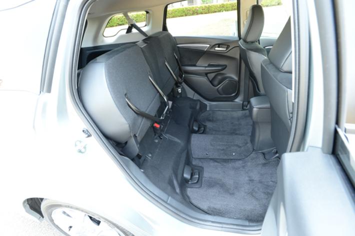 後席シートバックにある収納ケースもこれまた便利。小物などを入れておけるとあって、ユーザーのなかにも重宝しているひとも多いという, 2列目シートは座面を持ち上げるだけで簡単にシートアレンジができる機能も。女性でも片手で操作できるほど手軽なのだ