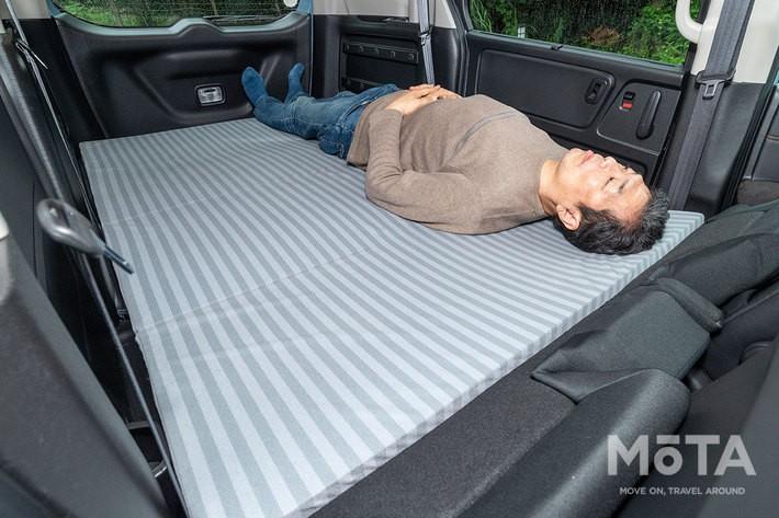 身長180cmの筆者が「ラゲッジクッションマット」に寝てみたところ。大人2名の就寝が余裕なことが写真からも伝わるだろう